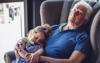 Little girl asleep on her granddad's lap. He is holding her in his arms while asleep in an armchair.