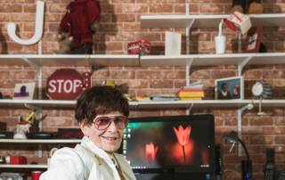 Judi Hindes, a resident of Masonic Village at Sewickley, sits in front of computer and brick wall.