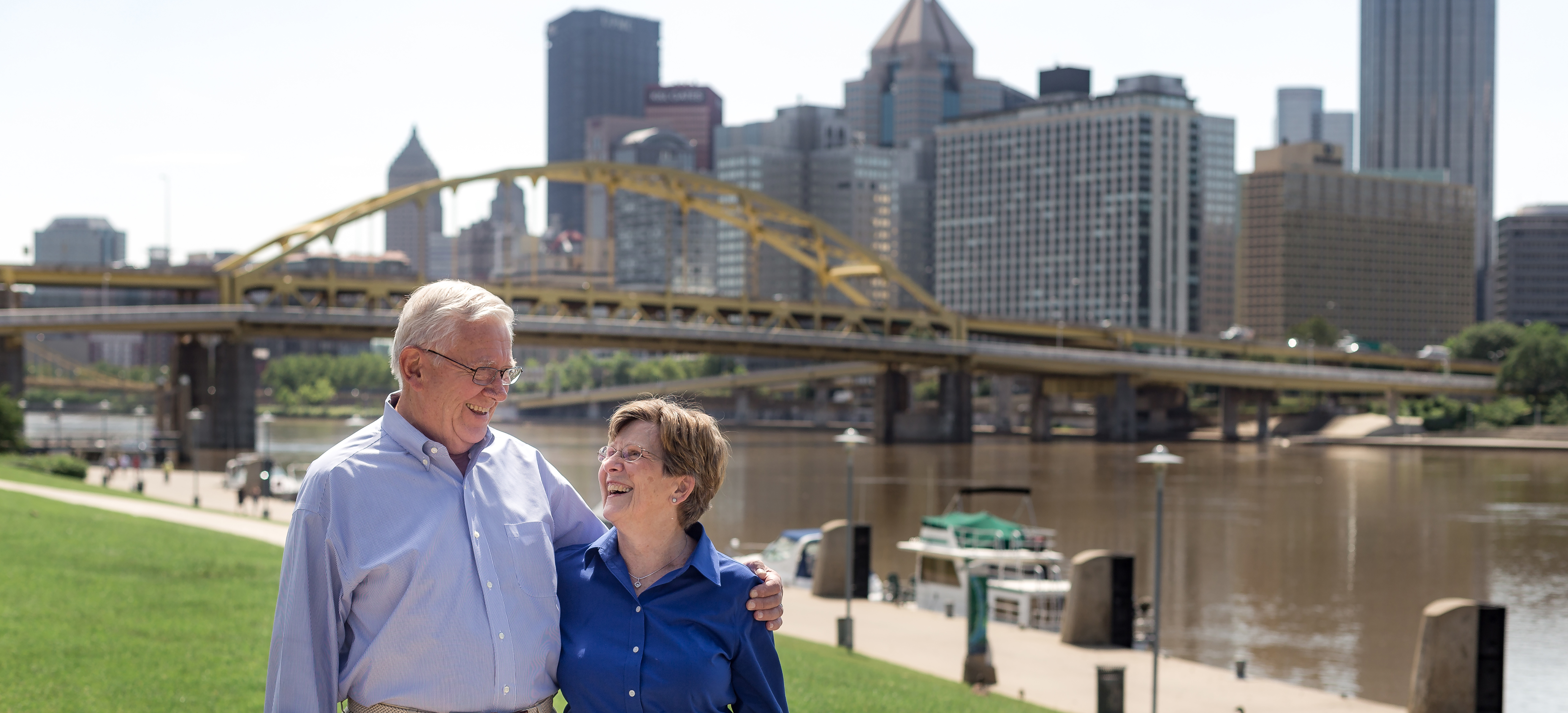 Couple stands outside and looks lovingly at each other in front large driving bridge. There is a river and a city in the background.