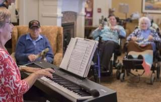 Residents and staff smile and laugh during a music therapy session at the Masonic Village at Elizabethtown.