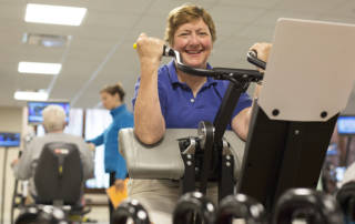 Woman on exercise bike smiling at camera