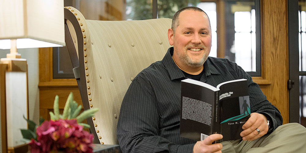 Todd Weitzel, Masonic Village at Elizabethtown, poses with his newly published book.