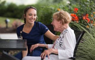 A nurse sits outside with a woman and they look at each other laughing