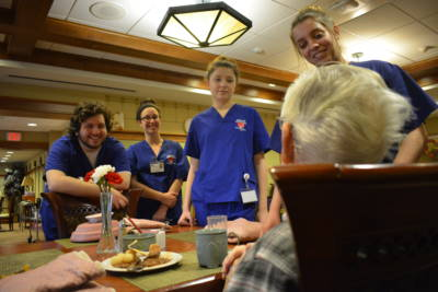 Nursing students talk with a resident