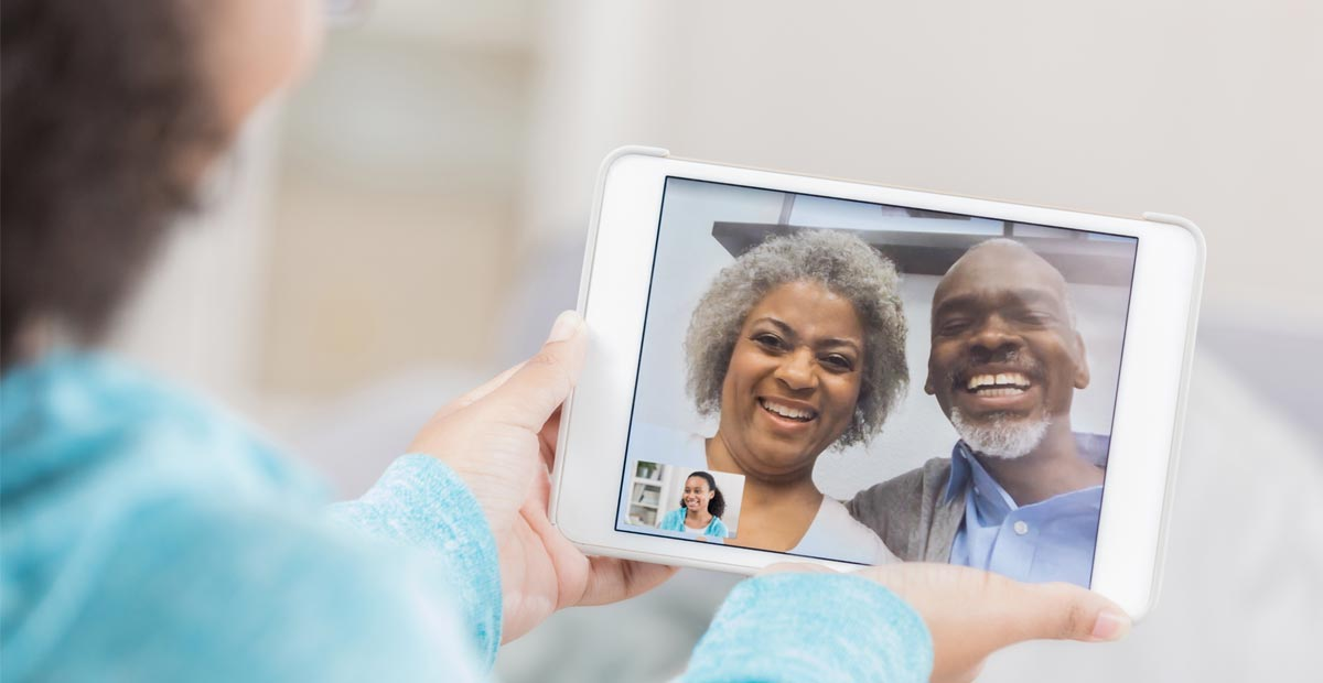 An older couple video chat with a tablet